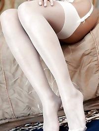 Sensational blonde posing only in sheer white stockings..
