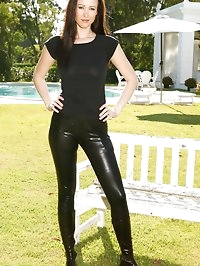 Brunette wearing black leather trousers and a tight black..